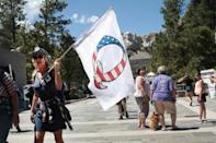 A Donald Trump supporter holding a QAnon flag at Mount Rushmore National Monument in South Dakota