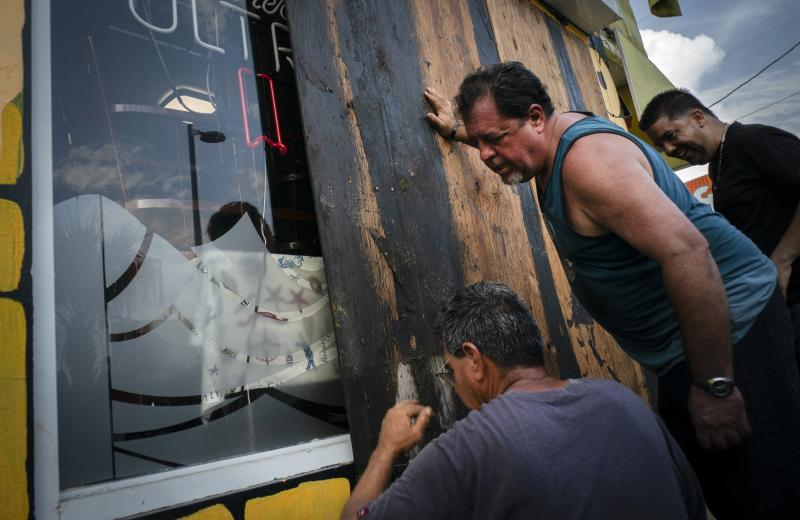 Men board up a shop's windows ahead of the arrival of Tropical Storm Dorian in Boqueron, Puerto Rico, Aug. 27, 2019. (Photo: Ramon Espinosa/AP)