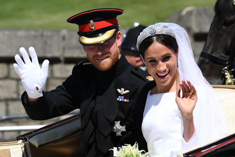 Britain's Prince Harry, Duke of Sussex and his wife Meghan, Duchess of Sussex wave from the Ascot Landau Carriage during their carriage procession on Castle Hill outside Windsor Castle in Windsor, on May 19, 2018 after their wedding ceremony. (Photo by Paul ELLIS / various sources / AFP) (Photo credit should read PAUL ELLIS/AFP/Getty Images)
