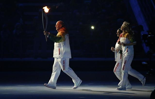 Russian wrestler Alexander Karelin carries the Olympic torch, followed by Russian tennis player Maria Sharapova, right, and Russian pole vaulter Yelena Isinbayeva during the opening ceremony of the 2014 Winter Olympics in Sochi, Russia, Friday, Feb. 7, 2014. (AP Photo/Mark Humphrey)