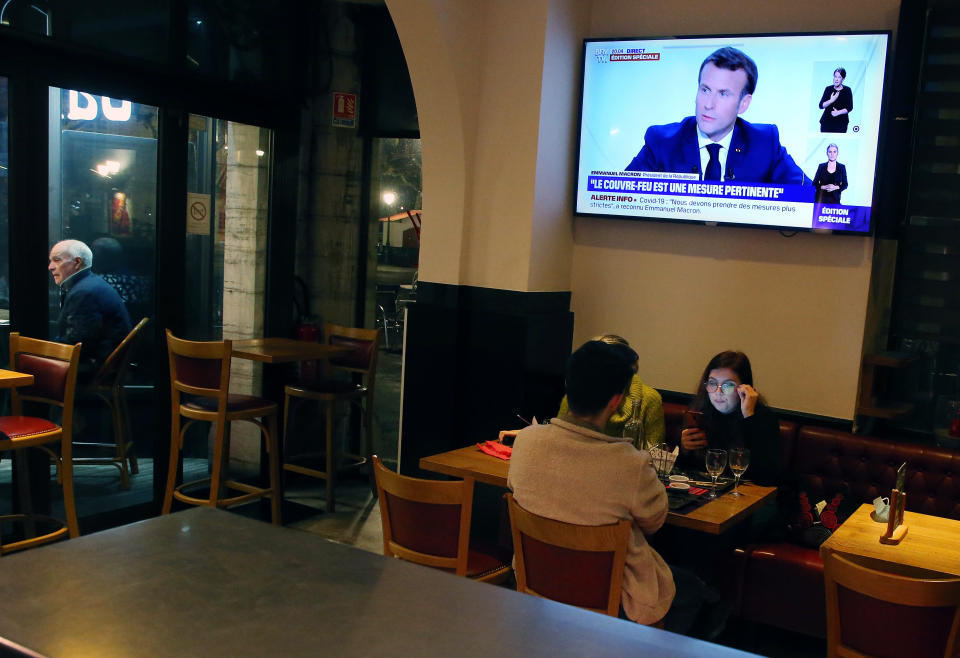 People dine at a restaurant as France's President Emmanuel Macron gives an address on television, in Saint jean de Luz, southwestern France, Wednesday, Oct. 14, 2020. Macron's office says France will restore a state of health emergency that expired on July 10. There are no additional measures that come into force with the move announced Wednesday, but it will allow the French government to enforce stricter measures in the future, either locally or nationally. (AP Photo/Bob Edme)