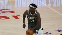 Milwaukee Bucks guard Jrue Holiday (21) controls the ball during an NBA basketball game against the Los Angeles Lakers Wednesday, March 31, 2021, in Los Angeles. (AP Photo/Ashley Landis)