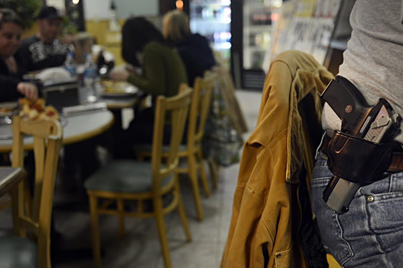 Kenneth Kormanis, right, had dinner with his wife and daughter at All Around Pizza in Virginia Beach, Va., on Monday, Feb. 18, 2013, where anyone who carries a gun or brings a concealed handgun permit is offered at 15 percent discount. (AP Photo/The Virginian-Pilot, Amanda Lucier) MAGS OUT