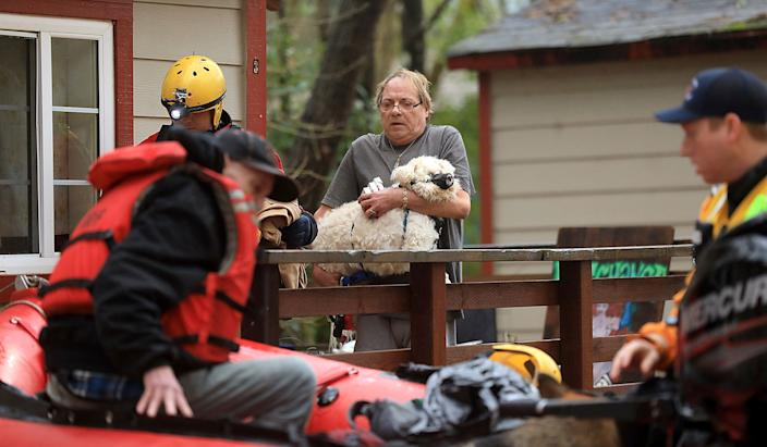 Ryan Lance, left, and Anthony Nash of the Russian River Fire Protection District swift water rescue team rescue residents of Sycamore Court Apartment in lower Guerneville, Calif., Feb. 27, 2019. (Photo: Kent Porter/The Press Democrat/AP)