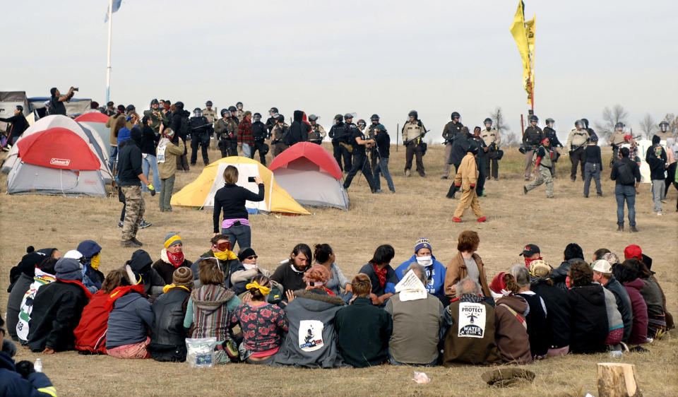 FILE - In this Oct. 27, 2016, file photo, Dakota Access Pipeline protesters sit in a prayer circle at the Front Line Camp as a line of law enforcement officers make their way across the camp to remove the protesters and relocate to the overflow camp a few miles to the south on Highway 1806 in Morton County, N.D. President Joe Biden has committed to regular and meaningful consultation with tribal nations on federal policies and projects that affect them. The Interior Department has scheduled a series of talks with tribes in March 2021 on health, the economy, racial justice and the environment. (Mike McCleary/The Bismarck Tribune via AP, File)