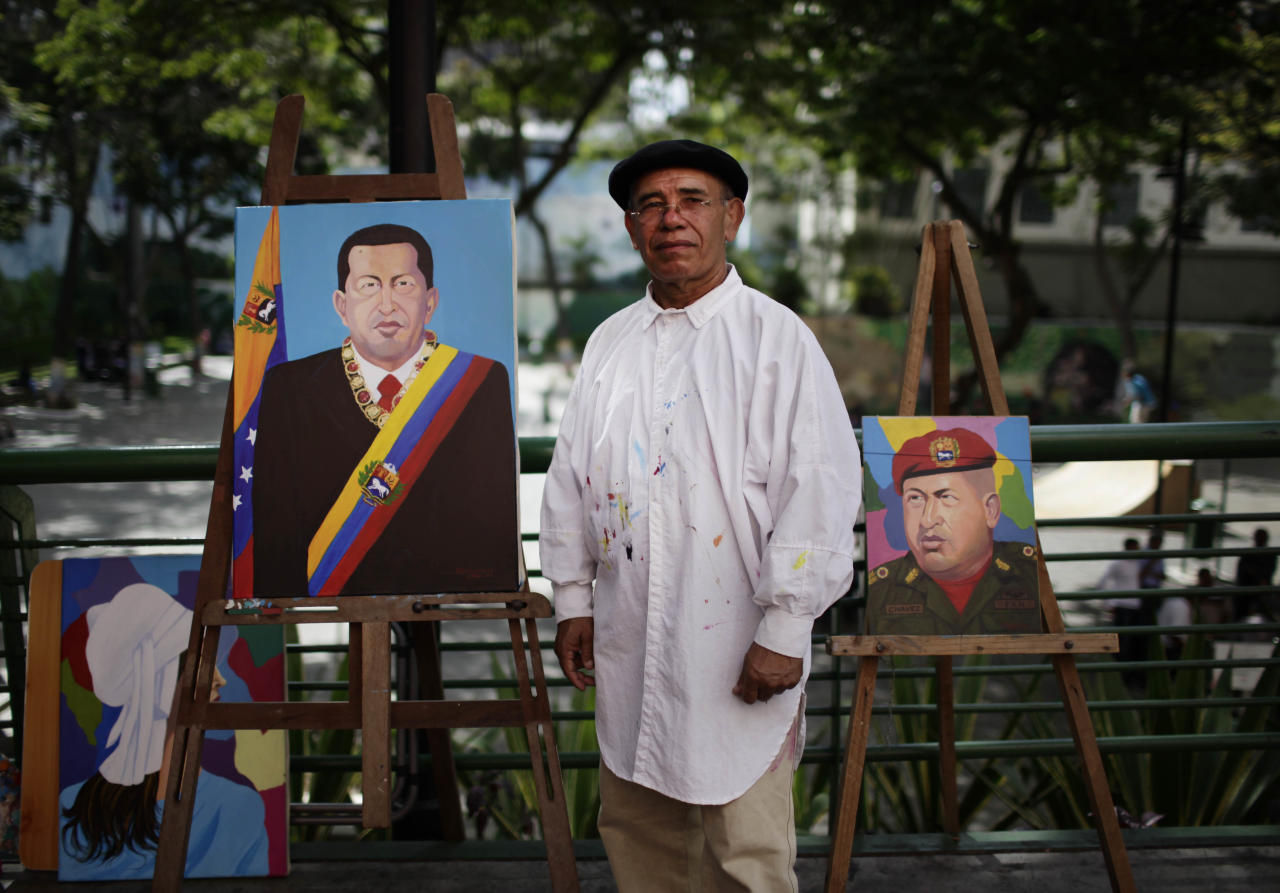 Venezuela artist Felix Rodriguez, 62, poses with his paintings of Venezuela's President Hugo Chavez on a street in Caracas, Venezuela, Friday March 2, 2012. Chavez has been in Cuba since last Friday to have a growth removed in the same part of the pelvis where a larger, malignant tumor was extracted last year. Chavez said Friday he's recovering quickly from tumor surgery, that doctors have put him on a special diet, and that he's taking daily walks. (AP Photo/Ariana Cubillos)