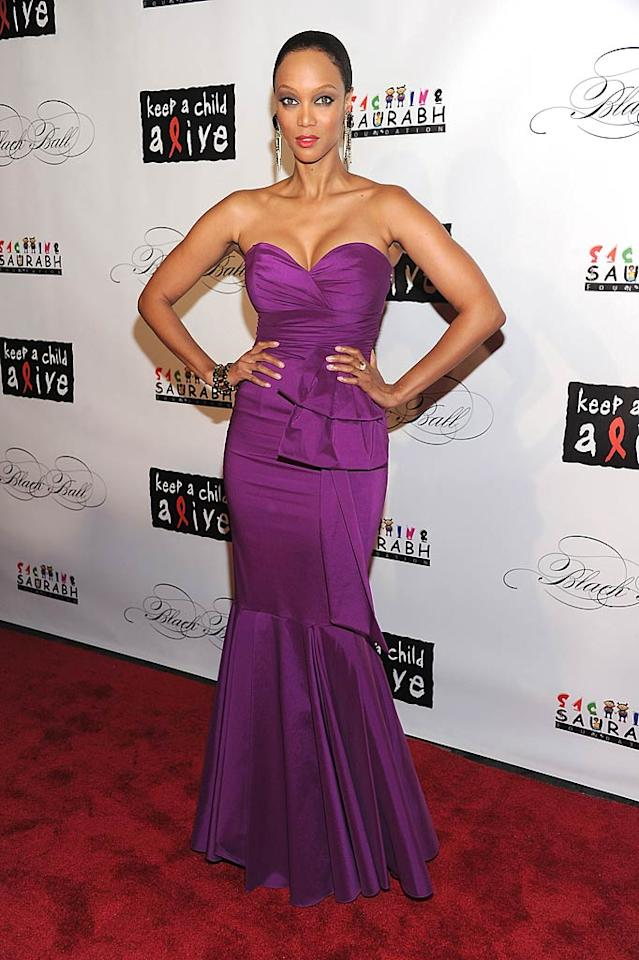 "Model-turned-author Tyra Banks popped a pose in a purple column gown. The ""America's Next Top Model"" host donated a makeover experience for the auction. (11/3/2011)"
