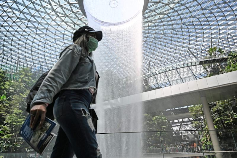 A traveller, wearing a protective facemask amid fears about the spread of the COVID-19 novel coronavirus, walks past the Rain Vortex display at Jewel Changi Airport in Singapore on February 27, 2020. (Photo by Roslan RAHMAN / AFP) (Photo by ROSLAN RAHMAN/AFP via Getty Images)