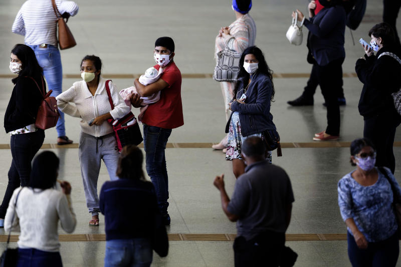 Commuters wear face masks at the bus station in Brasília, Brazil, Monday, May 11, 2020. Starting Monday, the capital city's government will fine or jail those who do not wear a face mask in public, amid the spread of the new coronavirus. (AP Photo/Eraldo Peres)