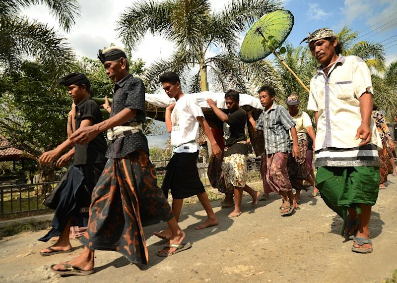 People carry an earthquake victim during a funeral in northern Lombok, Indonesia