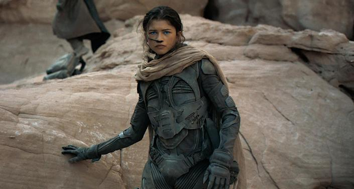 Zendaya in gear as she leans against a rock formation in a scene from Dune