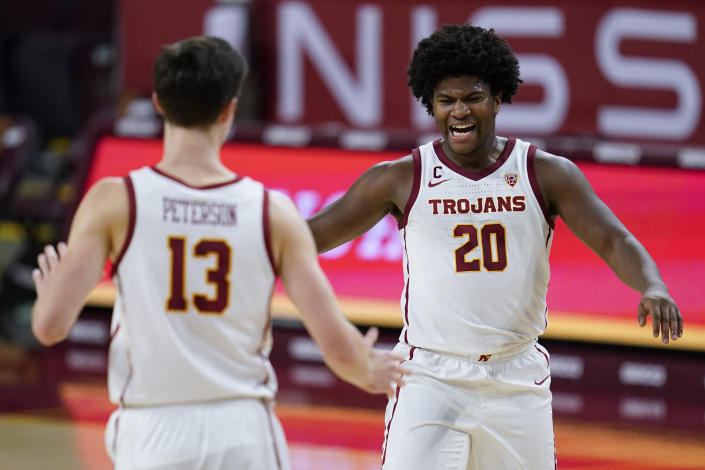 Southern California guard Drew Peterson (13) and guard Ethan Anderson (20) celebrate during a timeout in the first half of an NCAA college basketball game Monday, Feb. 22, 2021, in Los Angeles. (AP Photo/Ashley Landis)
