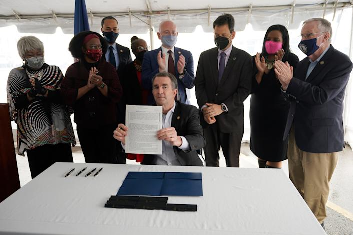 Virginia Gov. Ralph Northam, seated center, displays a bill abolishing the death penalty after signing it as he is surrounded by legislators and activists at Greensville Correctional Center in Jarratt, Va., Wednesday, March 24, 2021.