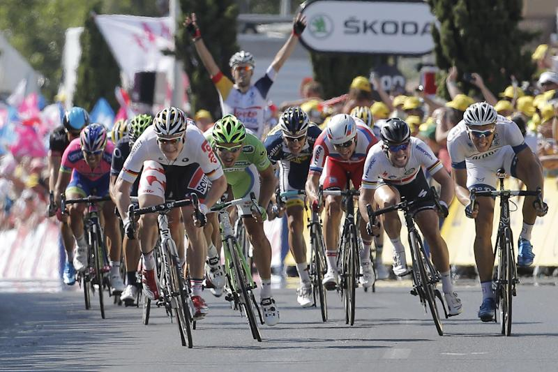 A teammate, rear, starts celebrating as Andre Greipel of Germany, left in white, as he sprints towards the finish line ahead Peter Sagan of Slovakia, center left in green and second place, Marcel Kittel of Germany, far left in white and third place and Mark Cavendish of Britain, second right and fourth place, to win the sixth stage of the Tour de France cycling race over 176.5 kilometers (110.3 miles) with start in Aix-en-Provence and finish in Montpellier, southern France, Thursday July 4, 2013. (AP Photo/Laurent Cipriani)