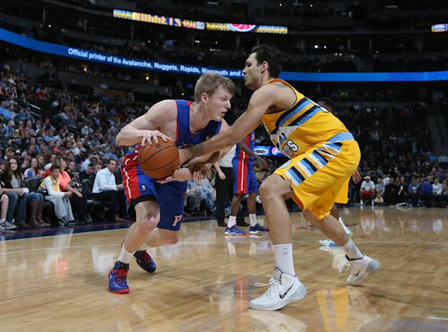 Detroit Pistons forward Kyle Singler, left, works the ball inside for a shot as Denver Nuggets guard Evan Fournier, of France, covers in the first quarter of an NBA basketball game in Denver on Wednesday, March 19, 2014. (AP Photo/David Zalubowski)