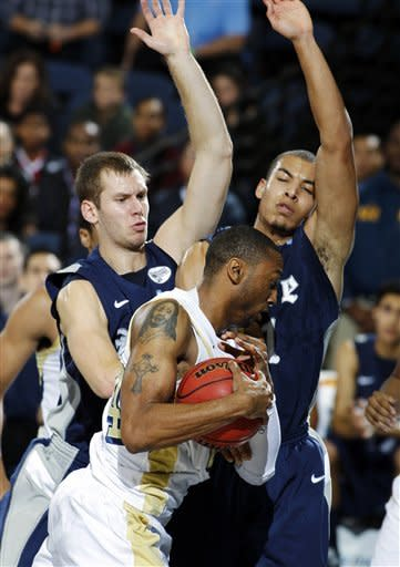 Rice forward Seth Gearhart, left, and forward Ross Wilson, right, defend Georgia Tech forward Kammeon Holsey, center, from getting to the basket during the first half of their NCAA college basketball game in the first round of the DirecTV Classic in Anaheim, Calif., Thursday, Nov. 22, 2012. (AP Photo/Alex Gallardo)