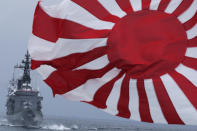 """FILE - In this Oct. 14, 2012, file photo, Japan Maritime Self-Defense Force (JMSDF) escort ship """"Kurama,"""" left, navigates behind destroyer """"Yudachi,"""" with a rising sun flag, during a fleet review in water off Sagami Bay, south of Tokyo. Japan's """"rising sun"""" flag is raising anger at the Olympics, with some of the host nation's neighbors calling for it to be banned during the Tokyo Games, which start Friday, July 23, 2021. (AP Photo/Itsuo Inouye, File)"""