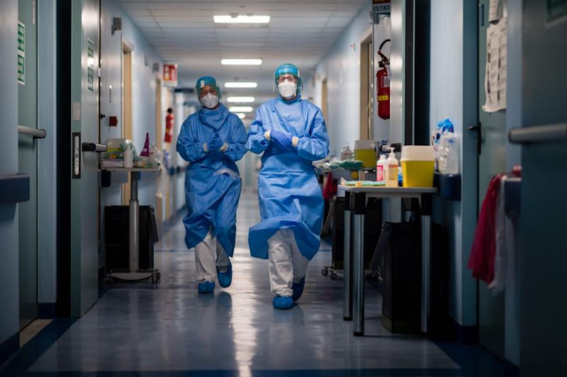 Nurses in protective gear walk down the hall at a hospital in Cremona, Italy. (Photo by Marco Mantovani/Getty Images)