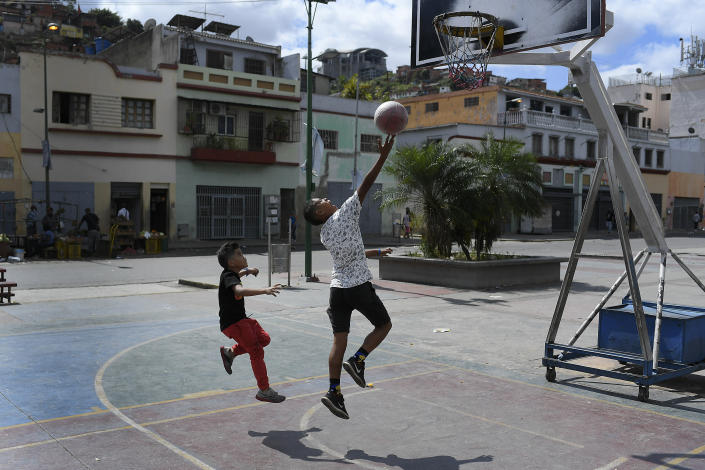 Children play a game of one on one on a public basketball court in the San Agustin neighborhood on Christmas Day in Caracas, Venezuela, Friday, Dec. 25, 2020, amid the new coronavirus pandemic. (AP Photo/Matias Delacroix)