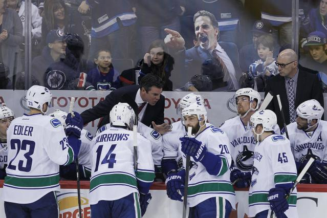 Winnipeg Jets fans taunt the Vancouver Canucks bench with an image of their suspended coach John Tortorella during a break in play in the first period of an NHL hockey game in Winnipeg, Manitoba, on Friday, Jan. 31, 2014. (AP Photo/The Canadian Press, John Woods)