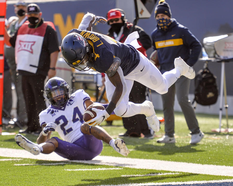 West Virginia running back Leddie Brown (4) is tackled by TCU safety Ar'Darius Washington (24) during the first half of an NCAA college football game on Saturday, Nov. 14, 2020, in Morgantown, W.Va. (William Wotring/The Dominion-Post via AP)