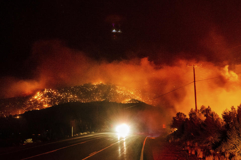 A car drives along Highway 395 as the Mountain View Fire tears through the Walker community in Mono County, Calif., on Tuesday, Nov. 17, 2020. (AP Photo/Noah Berger)