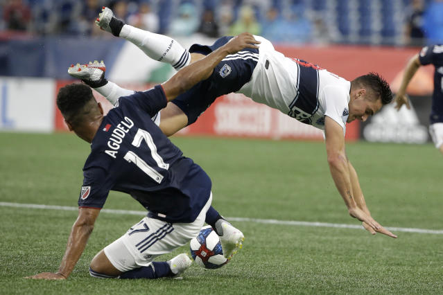 New England Revolution's Juan Agudelo, left, and Vancouver Whitecaps' Jake Nerwinski, right, vie for control of the ball during the first half of an MLS soccer match, Wednesday, July 17, 2019, in Foxborough, Mass. (AP Photo/Steven Senne)