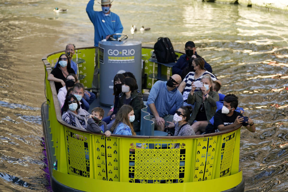Visitors wear face masks during the coronavirus pandemic as they travel along the River Walk, Wednesday, March 3, 2021, in San Antonio. Gov. Greg Abbott says Texas is lifting a mask mandate and lifting business capacity limits next week. (AP Photo/Eric Gay)