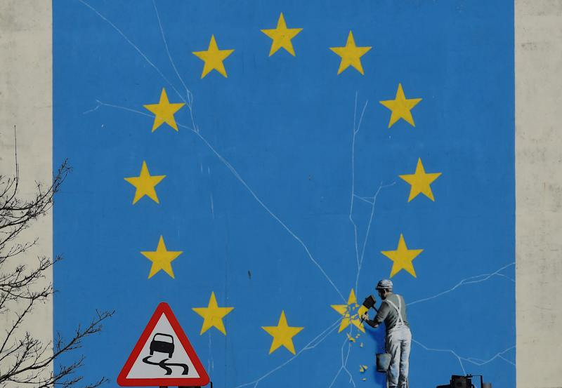 A road warning sign is seen in front of a large mural depicting the EU flag being chipped away, and attributed to the British artist Banksy at the Port of Dover, Britain, February 14, 2019. REUTERS/Toby Melville