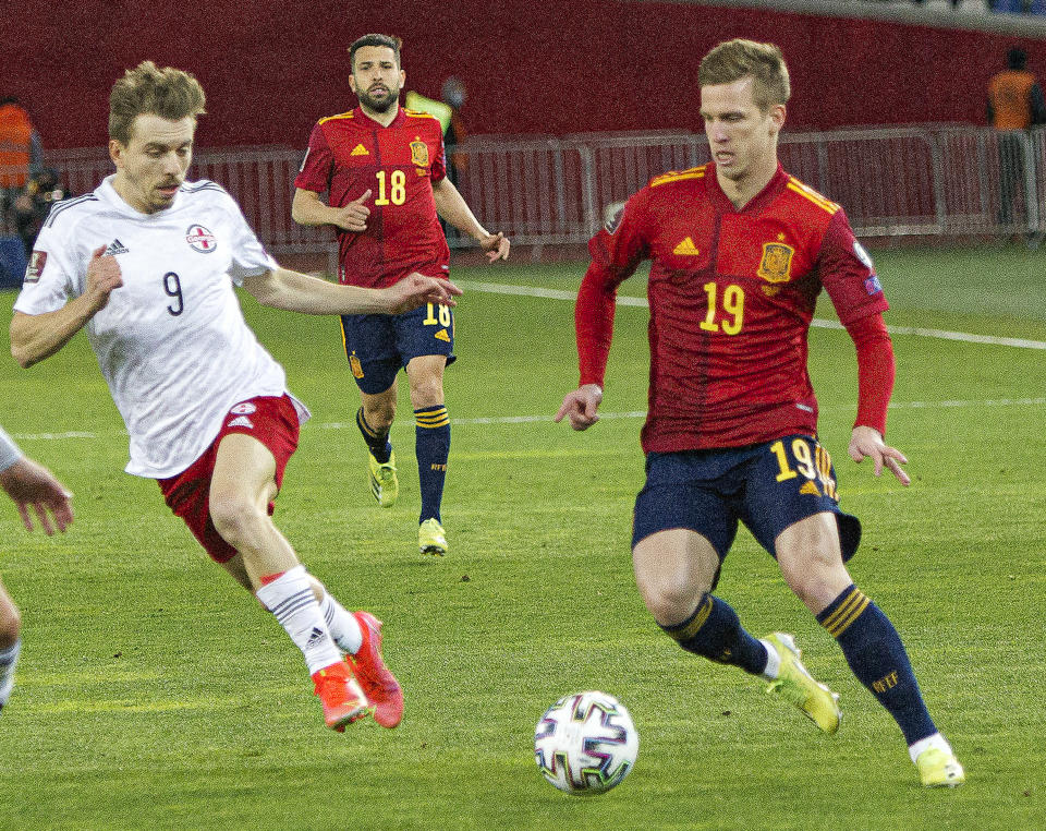 Georgia's Saba Lobzhanidze, left, and Spain's Dani Olmo challenge for the ball during the World Cup 2022 group B qualifying soccer match between Georgia and Spain at Boris Paichadze Dinamo Arena in Tbilisi, Georgia, Sunday, March 28, 2021. (AP Photo/Shakh Aivazov)