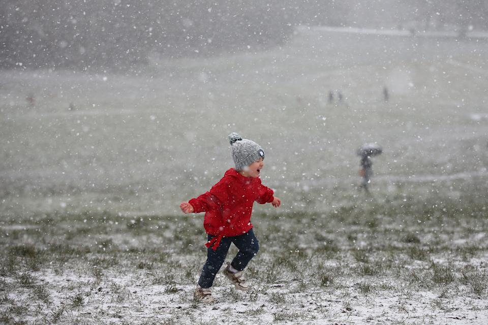 A child runs around as snow falls on Hampstead Heath in London. (Photo: Hollie Adams via Getty Images)