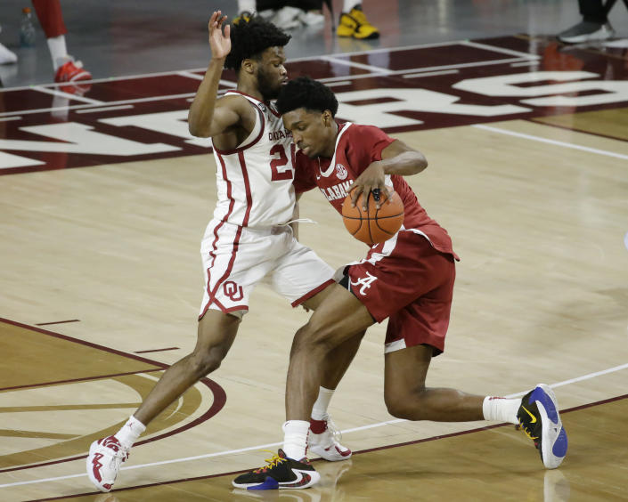 Alabama's Herbert Jones (1) goes against Oklahoma's Elijah Harkless (24) during the second half of an NCAA college basketball game in Norman, Okla., Saturday, Jan. 30, 2021. (AP Photo/Garett Fisbeck)