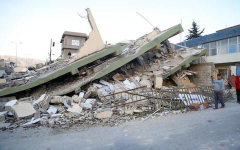 A collapsed house is seen hours after the 7.3 magnitude earthquake - Credit: Anadolu Agency/Getty Images