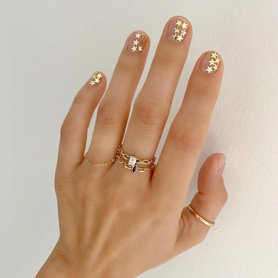 """When you don't feel like reaching for a bright color, glittery stars make enough of a splash. Amazon is full of <a href=""""https://www.amazon.com/Lookathot-Pattern-Sequins-Manicure-Decoration/dp/B07CMC2CDL/ref=sr_1_2?dchild=1&keywords=gold+star+sequins+nails&qid=1606331707&sr=8-2"""" rel=""""nofollow noopener"""" target=""""_blank"""" data-ylk=""""slk:nail sequins"""" class=""""link rapid-noclick-resp"""">nail sequins</a> in tons of shapes and sizes."""