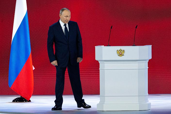 <p>Russian president Vladimir Putin leaves the hall after his annual state of the nation address today (21 April)</p> (AP)