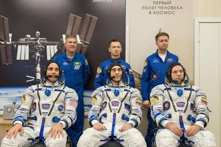Expedition 63 crew members Chris Cassidy of NASA, seated left, and Anatoly Ivanishin and Ivan Vagner of Roscosmos, seated right, pose for a photo with backup crew members Steve Bowen of NASA, standing left, and Sergey Ryzhikov and Andrei Babkin of Roscosmos, standing right, after the crew had its Sokol suits pressure checked prior to launch on a Soyuz rocket, Thursday, April 9, 2020.