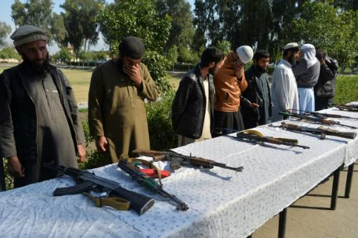 Former Afghan Taliban fighters in Jalalabad stand next to weapons before handing them over as part of a government peace and reconciliation process