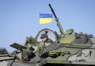 A Ukrainian soldier rides on an armoured personnel carrier during a military exercise near the village of Goncharivske March 14, 2014. U.S. President Barack Obama said on Friday he still hopes for a diplomatic solution to the Ukraine crisis heading into a pivotal weekend. REUTERS/Gleb Garanich