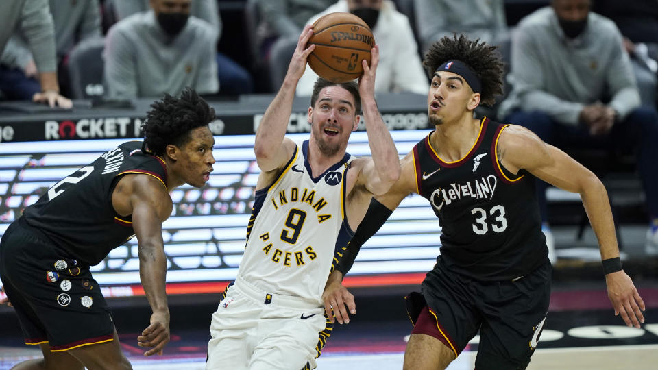 Indiana Pacers' T.J. McConnell (9) drives between Cleveland Cavaliers' Collin Sexton (2) and Brodric Thomas (33) in the second half of an NBA basketball game, Monday, May 10, 2021, in Cleveland. (AP Photo/Tony Dejak)