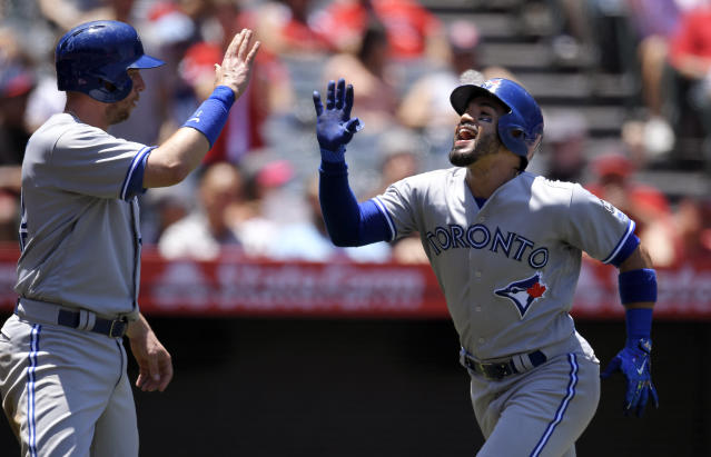 CORRECTS PLAYER AT LEFT TO JUSTIN SMOAK-Toronto Blue Jays' Devon Travis, right, is congratulated by Justin Smoak after hitting a three-run home run during the second inning of a baseball game against the Los Angeles Angels Sunday, June 24, 2018, in Anaheim, Calif. (AP Photo/Mark J. Terrill)