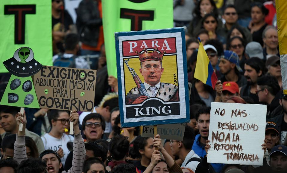 A demonstrator holds a banner depicting Colombian ex-president Alvaro Uribe during a protest against a tax reform currently being discussed in the country, outside the Congress in Bogota on December 16, 2019. - The government of Colombian President Ivan Duque has been facing protests against his economic policies, unemployment, political corruption and drug-financed violence. (Photo by Juan BARRETO / AFP) (Photo by JUAN BARRETO/AFP via Getty Images)