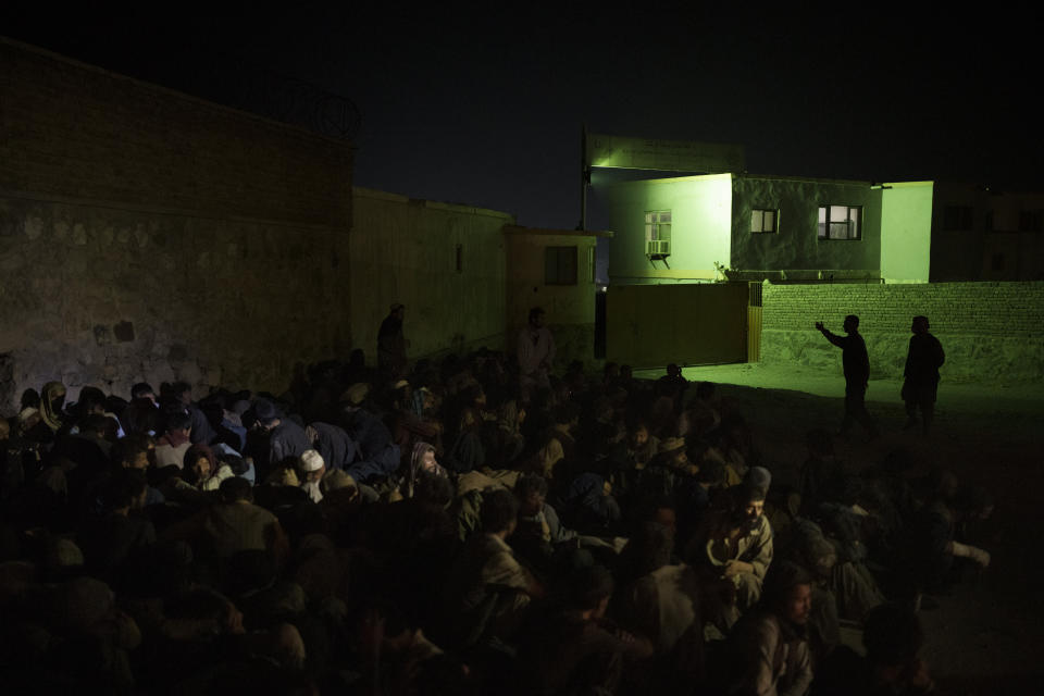 Taliban fighters, top right, gesture to dozens of drug users detained at a police station in Kabul, Afghanistan, Friday, Oct. 1, 2021. The Taliban are shifting from being warriors to an urban police force. (AP Photo/Felipe Dana)