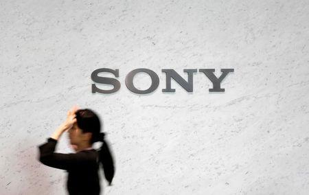 FILE PHOTO -  A reception staff walks under a logo of Sony Corp at its headquarters in Tokyo