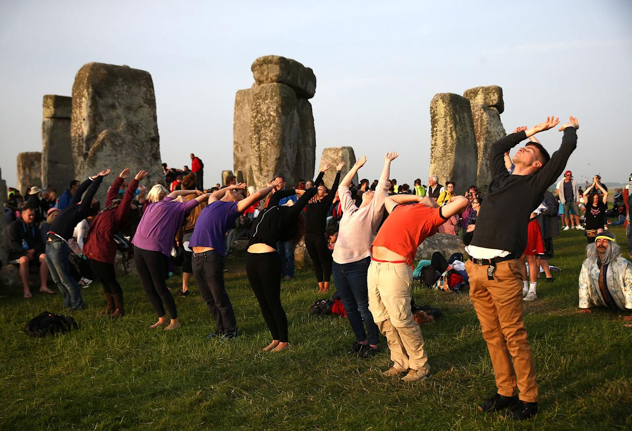 <p>People practice yoga by the stones of the Stonehenge monument at dawn on the summer solstice near Amesbury, Britain, June 21, 2017. (Photo: Neil Hall/Reuters) </p>