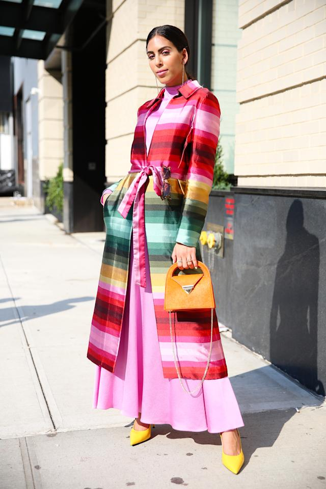 A guest is seen posing in a colourfulrcoat and orange purse at Spring Studios. [Photo: Getty]