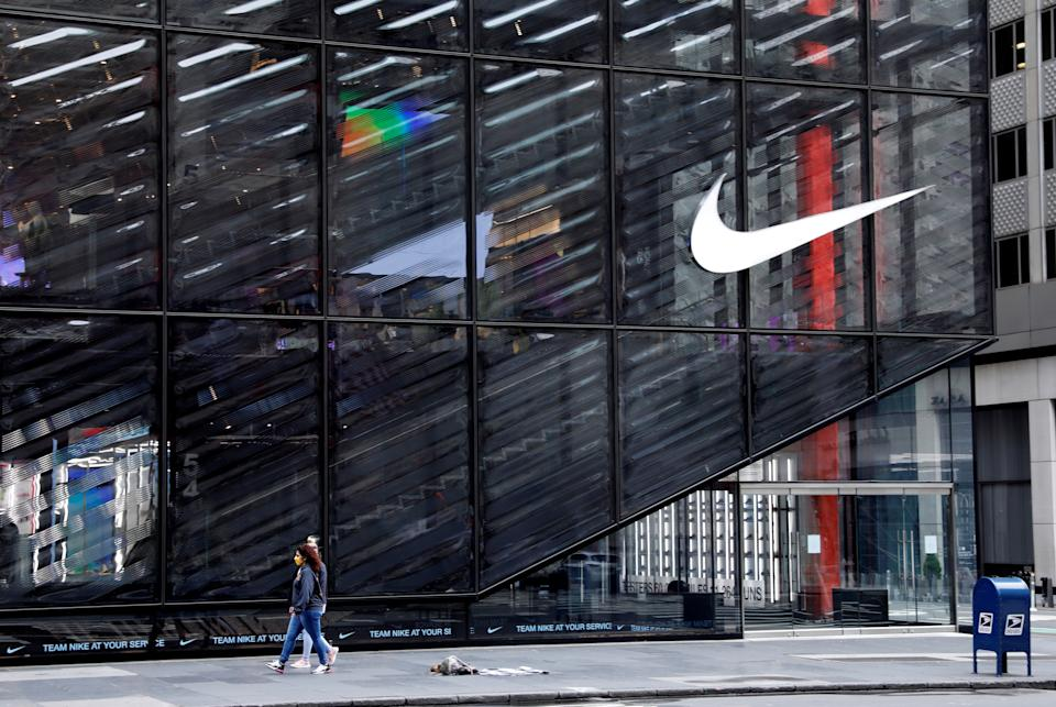 People wearing protective face masks walk past the closed Nike store on a nearly empty 5th Avenue, during the outbreak of the coronavirus disease (COVID-19), in Manhattan, New York city, New York, U.S., May 11, 2020. REUTERS/Mike Segar