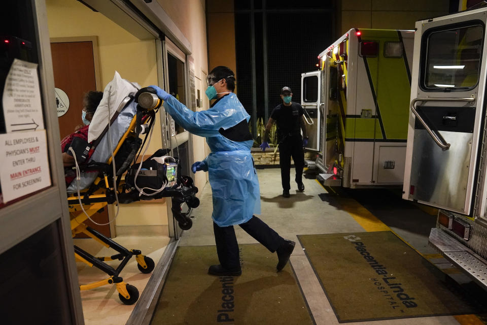 FILE - In this Jan. 8, 2021, file photo, emergency medical technician Thomas Hoang, 29, of Emergency Ambulance Service, pushes a gurney into an emergency room to drop off a COVID-19 patient in Placentia, Calif. Coronavirus hospitalizations are falling across the United States, but deaths have remained stubbornly high. (AP Photo/Jae C. Hong, File)