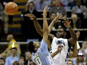 North Carolina's Nate Britt (0) guards as UNC Wilmington's Addison Spruill passes during the first half of an NCAA college basketball game in Chapel Hill, N.C., Tuesday, Dec. 31, 2013. (AP Photo/Gerry Broome)