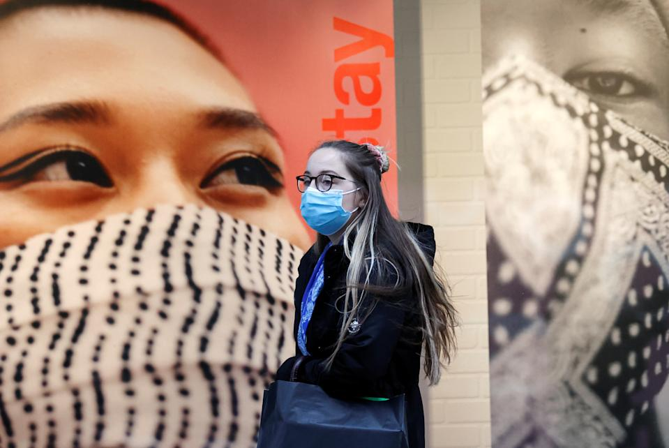 A woman wearing a protective face mask walks on the street amid the outbreak of the coronavirus disease (COVID-19), in Liverpool, Britain October 13, 2020. REUTERS/Phil Noble