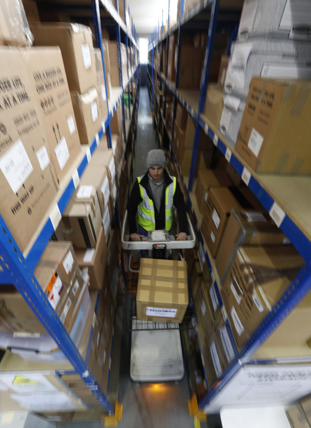 Lovespace warehouse worker Piotr Waligora, works on an electronic lift to place boxes and goods in their allocated zones at the warehouse in Dunstable, England Monday, Jan. 14, 2019. Lovespace, which collects boxes from customers, stores them and then returns the goods when needed, says revenue from businesses doubled over the past year as enterprises large and small began stockpiling inventory because of concerns they will be cut off from suppliers if Britain leaves the European Union without an agreement on future trading relations. (AP Photo/Alastair Grant)